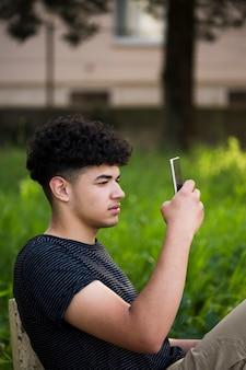 Junger ethnischer gelockter mann, der foto auf bank macht