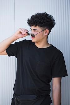 Junger ethnischer gelockter mann im schwarzen hemd gläser entfernend