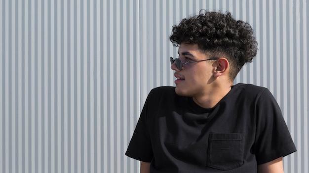 Junger ethnischer gelockter mann im schwarzen hemd und in der sonnenbrille