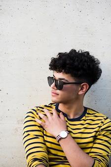 Junger ethnischer gelockter mann in der sonnenbrille und im gestreiften sweatshirt
