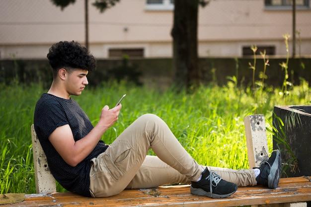 Junger ethnischer mann, der auf bank sitzt und smartphone verwendet