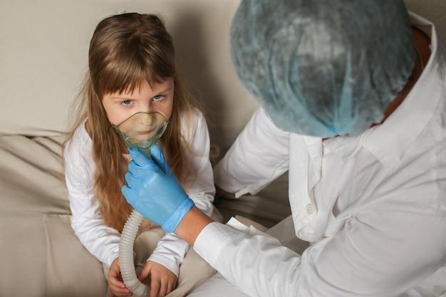 Junger europäischer arzt, der einem kleinen mädchen mit einem sprühmaskenarzt hilft, der inhalationsmedikationstherapie auf kleines mädchen mit inhalationstherapie für asthma mit inhalatormaske anwendet