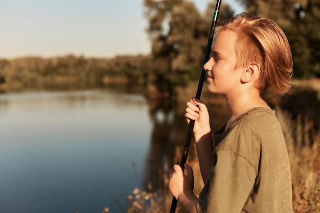 Junger europäischer blonder junge, der im sonnigen sommertag fischt, in der ferne schaut, seine freizeit genießt, grünes t-shirt trägt, am ufer des flusses nahe wasser steht.