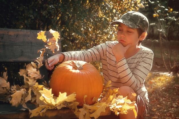Junger europäischer junge im gestreiften kurzen verziert großen halloween-kürbis mit gelbem herbstlaub