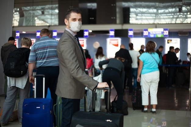 Junger europäischer mann in der medizinischen schutzmaske im flughafen. angst vor dem gefährlichen covid-19-influenza-coronavirus