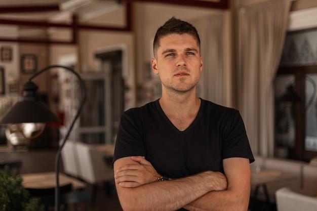 Junger europäischer mann mit stilvoller frisur in einem schwarzen t-shirt steht in einem weinlese-restaurant
