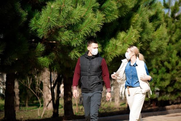 Junger europäischer mann und frau in der medizinischen einwegmaske, die im freien geht, fürchtet vor gefährlichem ncov 2019 influenza coronavirus, das in china mutiert ist und sich ausbreitet.