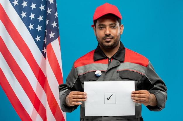 Junger fabrikarbeiter gemischter abstammung in arbeitskleidung, der ihnen seinen stimmzettel mit zecke in einem der quadrate zeigt, während er gegen amerikanische flagge steht