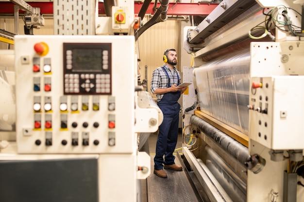 Junger fabrikingenieur in arbeitskleidung, der an der verarbeitungslinie bereitsteht, während er neues produktionssystem oder neue technologie testet