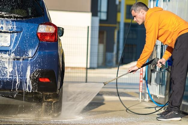 Junger fahrer, der sein auto mit kontaktlosem hochdruckwasserstrahl in der selbstbedienungswaschanlage wäscht.