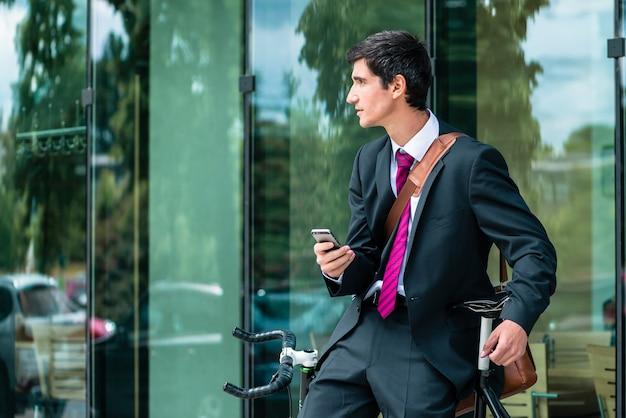 Junger firmenangestellter, der ein mobiltelefon hält, während draußen in einer modernen europäischen stadt wartet