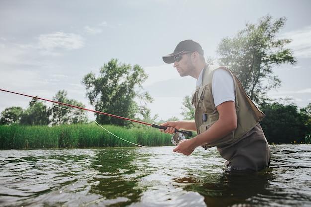 Junger fischer, der auf see oder fluss fischt. aktiver kerl im gewand, der rute benutzt, um leckeren köstlichen fisch zu fangen. steh im tiefen wasser. sommeraktivität.