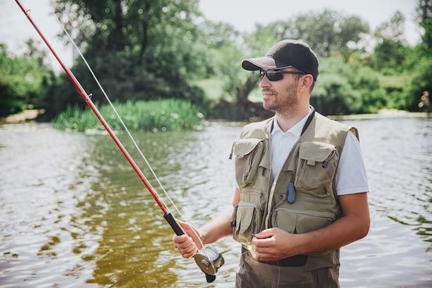 Junger fischer, der auf see oder fluss fischt. bild des ernsten professionellen kerls, der stab in händen hält und auf fisch wartet. steht im fluss- oder seewasser. leckere leckere fische fangen.