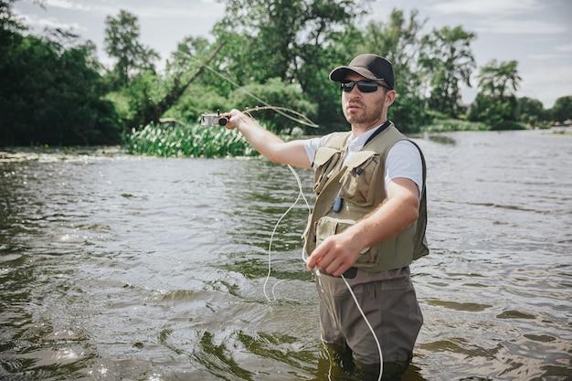 Junger fischer, der auf see oder fluss fischt. bild des ernsthaften konzentrierten kerls im angelroboter steht im wasser und benutzt rute für fischjagd. sonniger sommertag.