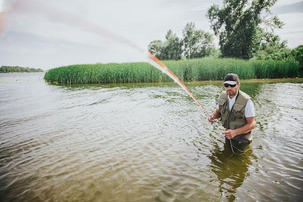 Junger fischer, der auf see oder fluss fischt. bild des kerls im gewand, der angelschnur gerade zur kamera hält. mann stehen im wasser in der mitte des sees oder des flusses. angelzeit im sommer.