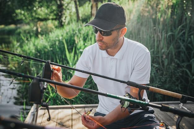Junger fischer, der auf see oder fluss fischt. bild des kerls in der mütze und in der sonnenbrille, die rolle und köder mit ruten vor dem fischen einstellen. allein vor der angelausrüstung sitzen. tageslicht und sonniger tag.