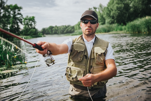 Junger fischer, der auf see oder fluss fischt. bild des mannes, der aktives fischen mit haltestange in der hand tut. stehen sie alleine in der mitte des flusses oder sees. ernsthaft konzentriertes angeln.