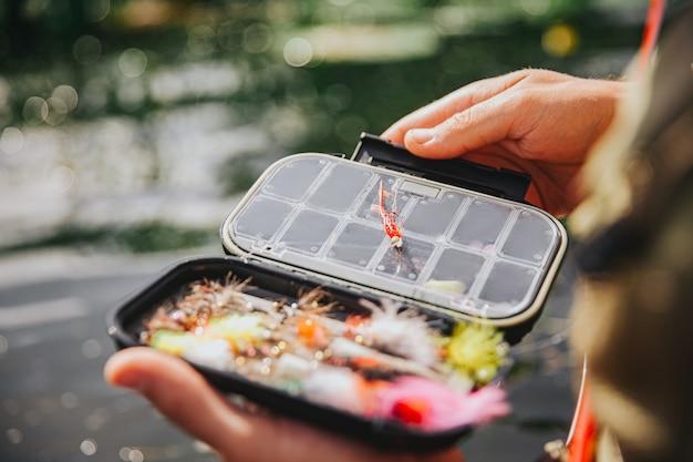 Junger fischer, der auf see oder fluss fischt. bild von plastikködern in der box für die angelzeit. kerl hält es in händen und zeigt vor der kamera. im wasser stehen. tageslicht.