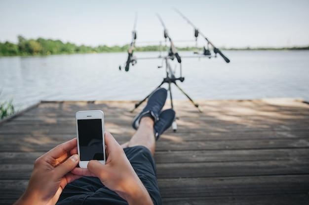 Junger fischer, der auf see oder fluss fischt. eine ansicht der augen des kerls, die auf pier sitzen und smartphone benutzen. ich warte darauf, ein paar fische zu fangen. kerl mit drei angelruten für die wasserjagd. schöner sonniger tag