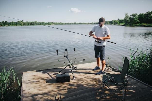 Junger fischer, der auf see oder fluss fischt. ernsthafter beschäftigter kerl, der angelrolle für fischereiprozess am see oder am fluss einstellt. mann hält stab in händen und arbeitet daran. stehend am see- oder flusswasser.