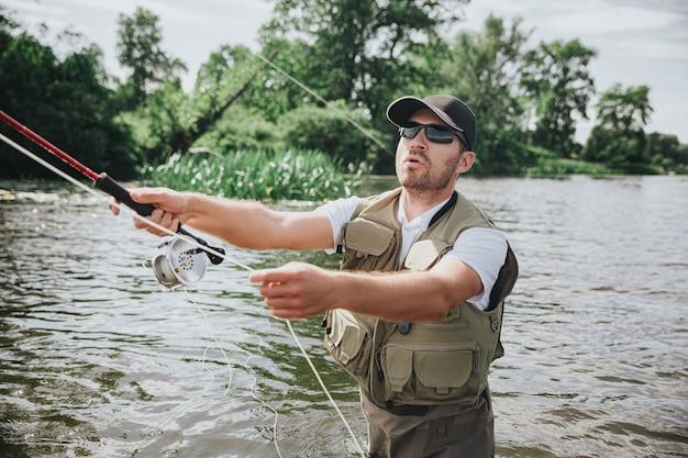 Junger fischer, der auf see oder fluss fischt. ernsthafter konzentrierter kerl, der rute in händen hält und sie für das fischen verwendet. wasserjagd mitten im see oder fluss.