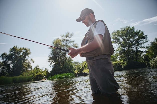 Junger fischer, der auf see oder fluss fischt. erwachsener kerl in fischerkleidung und mütze, die stab in händen hält. verwenden sie köder zum fangen von fischen. mand steht im fluss- oder seewasser. schöner sonniger tag.