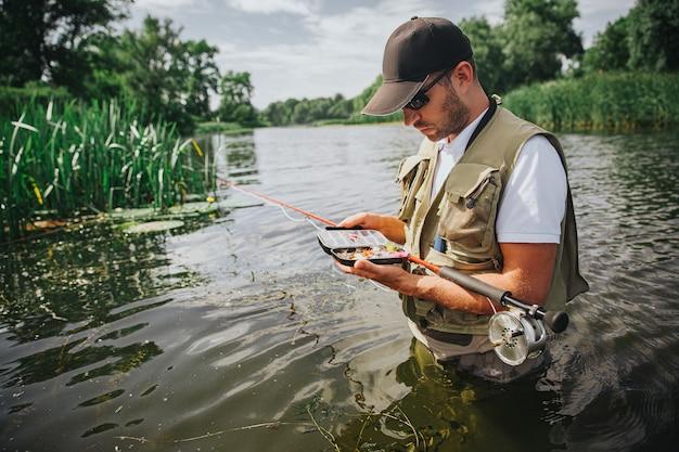Junger fischer, der auf see oder fluss fischt. konzentrierte beschäftigte kerl halten geöffnete schachtel mit plastikködern zum angeln. mann stehen im tiefen wasser in der mitte des flusses oder des sees.