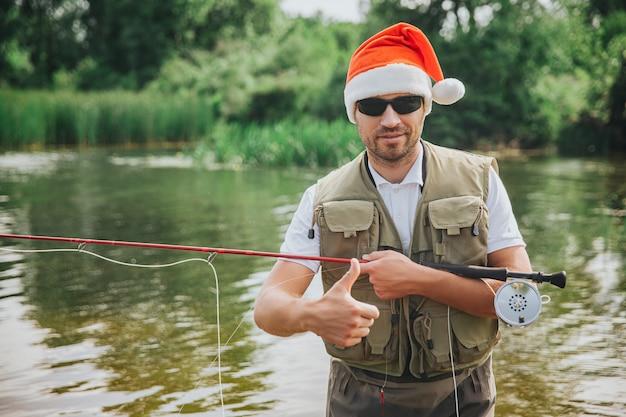 Junger fischer, der auf see oder fluss fischt. neujahr oder weihnachtszeit. kerl hält rute zum angeln. festliche zeit in den ferien. 2021 feiern.