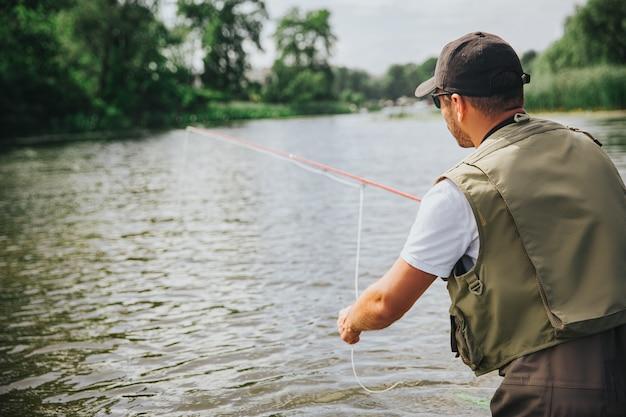 Junger fischer, der auf see oder fluss fischt. rückansicht des kerls, der wasser betrachtet und allein fischt. stange in händen halten. ruhige friedliche sommernatur. sonnenschein und tageslicht.