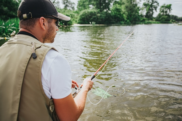 Junger fischer, der auf see oder fluss fischt. rückansicht des konzentrierten kerls, der wartet, um einige fische zu fangen. mann, der angelrute in händen hält. sonniger tag am fluss oder see.