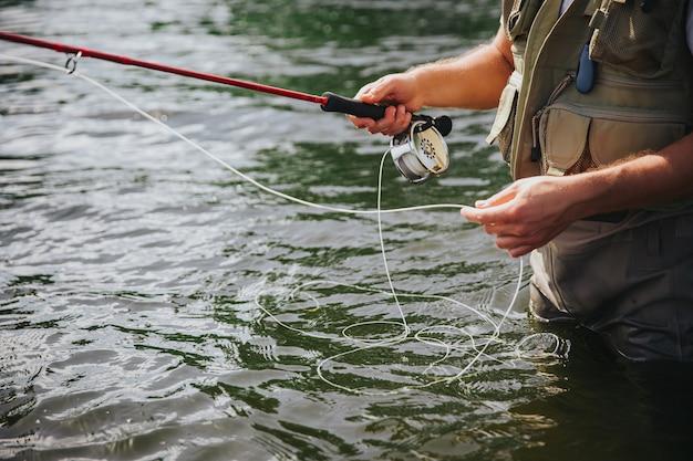 Junger fischer, der auf see oder fluss fischt. schnittansicht der hände des kerls, die angelschnur halten. vorbereitung, um fluss- oder seefische zu fangen. mann stehen in frischem wasser.