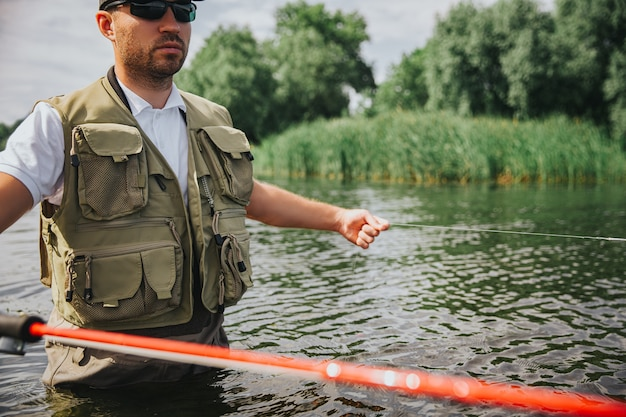 Junger fischer, der auf see oder fluss fischt. schnittansicht des kerls, der lange rote stange hält und allein in der mitte des sees oder des flusses fischt. im wasser stehen. schöner sonniger tag.