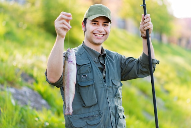 Junger fischer, der einen fisch abfängt
