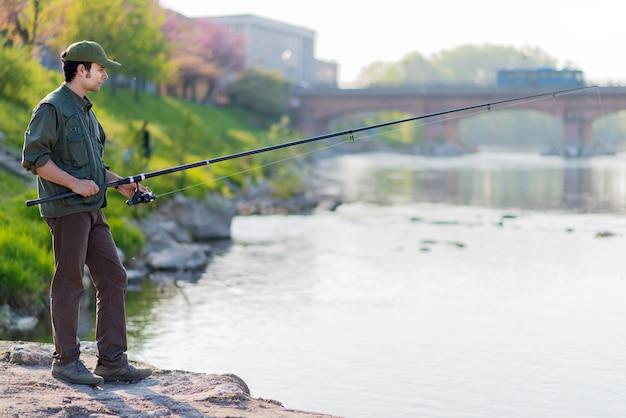 Junger fischer in dem fluss