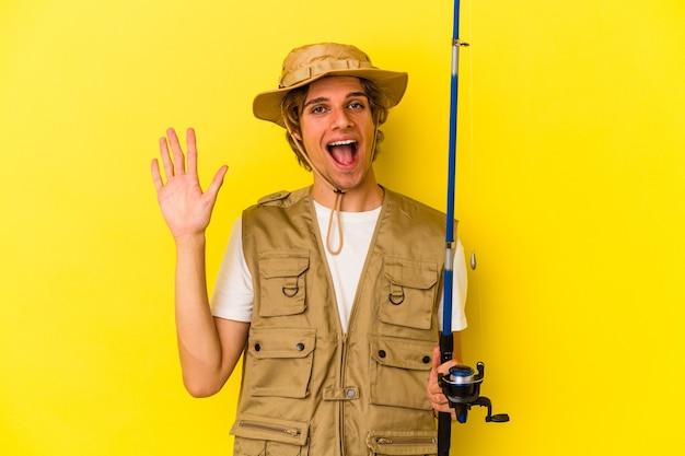 Junger fischer mit make-up-haltestange isoliert auf gelbem hintergrund lächelnd fröhlich mit nummer fünf mit den fingern.