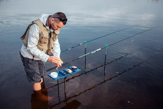 Junger fischer steht barfuß im wasser. er lehnt sich an eine geöffnete plastikbox mit künstlichen ködern. es gibt zwei fliegenruten, die in haken liegen.