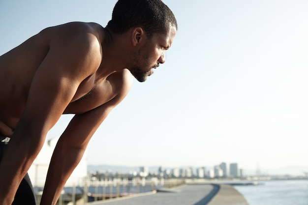 Junger fit mann am strand, der die landschaft bewundert
