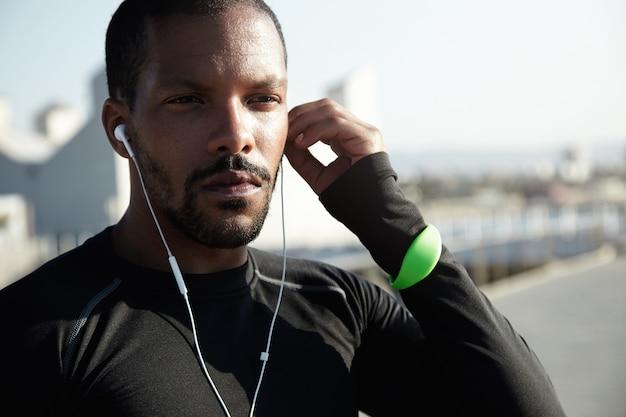 Junger fit mann am strand, der musik hört
