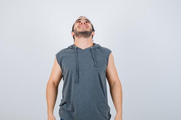 Junger fit mann, der im ärmellosen kapuzenpulli nach oben starrt und fröhlich aussieht. vorderansicht.