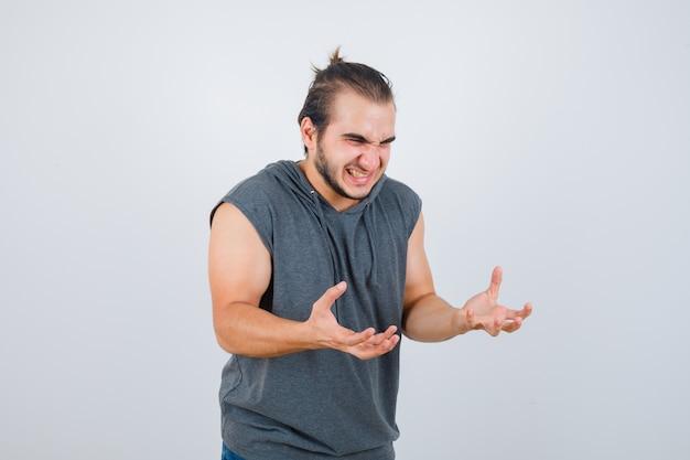 Junger fit mann hält hände in aggressiver weise in ärmellosem hoodie und sieht wütend aus. vorderansicht.