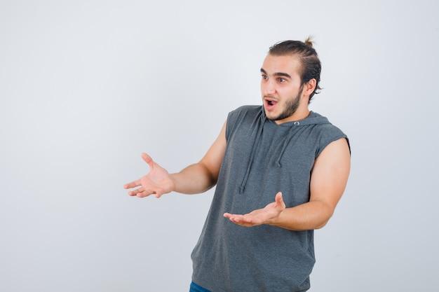 Junger fit mann macht empfangsgeste im ärmellosen hoodie und sieht schockiert aus. vorderansicht.