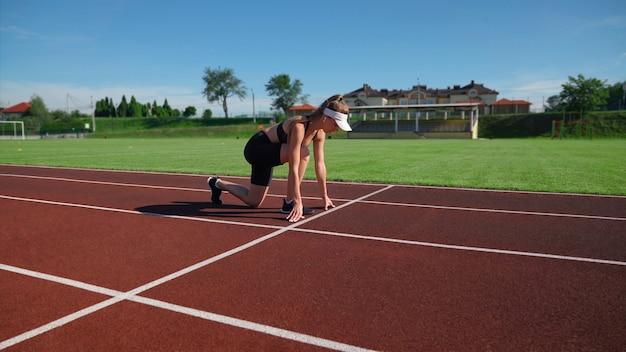Junger fit weiblicher sprinter, der rennen auf der rennstrecke im stadion am sonnigen sommertag startet. seitenansicht der aktiven athletischen frau, die sprinterposition übt, die für lauf vorbereitet. konzept des sports.