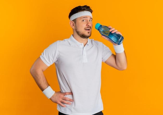 Junger fitness-mann im weißen hemd mit dem stirnband, das flasche wasser hält, das kamera mit lächeln auf gesicht steht, das über orange hintergrund steht