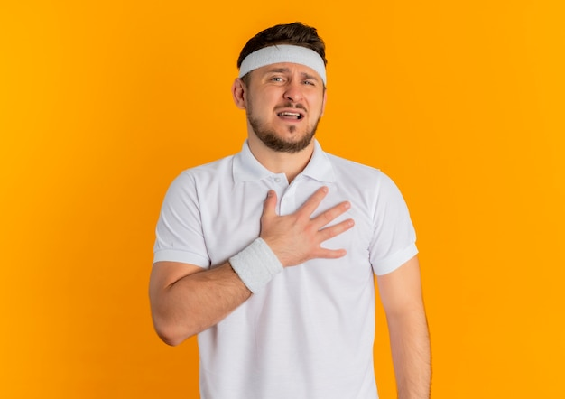 Junger fitness-mann im weißen hemd mit dem stirnband, das hand auf seiner brust betrachtet, die kamera müde und erschöpft über orange hintergrund stehend betrachtet