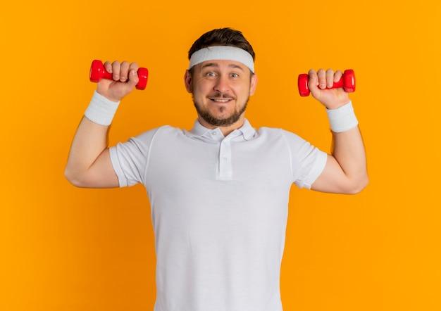 Junger fitness-mann im weißen hemd mit dem stirnband, das mit den hanteln arbeitet, die sicher lächelnd über orange wand stehen