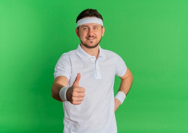 Junger fitness-mann im weißen hemd mit dem stirnband, das nach vorne mit lächeln auf gesicht schaut, das daumen oben steht über grüner wand zeigt