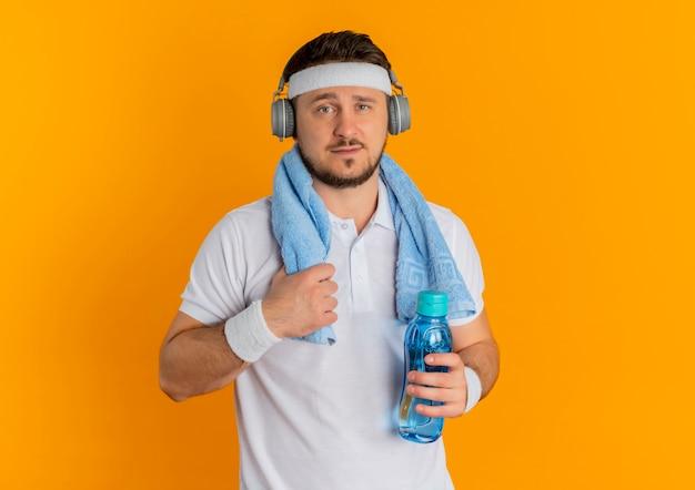 Junger fitness-mann im weißen hemd mit dem stirnband und dem handtuch um den hals, der flasche wasser hält, die kamera mit dem sicheren ausdruck steht, der über orange hintergrund steht