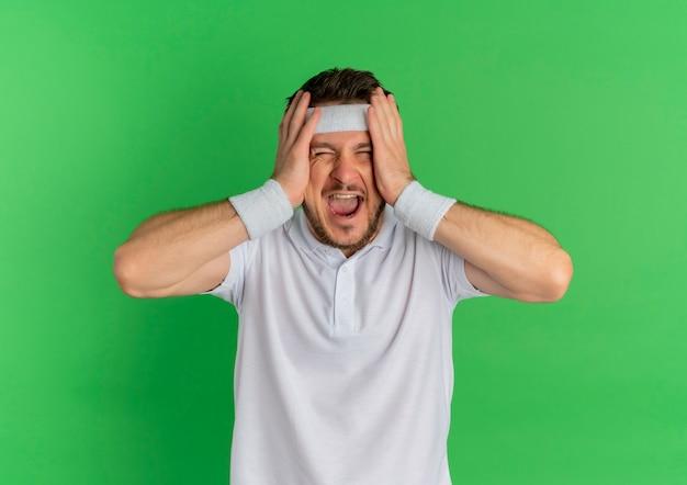 Junger fitness-mann im weißen hemd mit stirnband crazu glücklich schreiend für erfolg, der über grünem hintergrund steht
