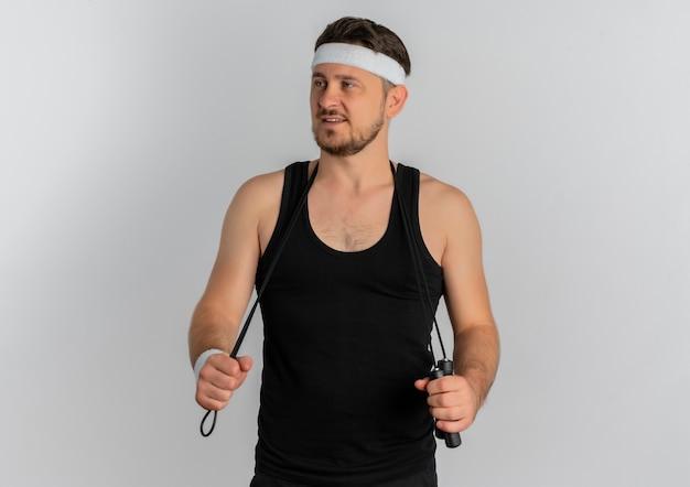 Junger fitness-mann mit dem stirnband, das das überspringen schaut, das sicher steht, über weißem hintergrund zu stehen