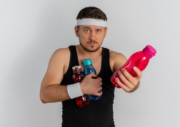 Junger fitness-mann mit dem stirnband, der flaschen des wassers hält, das verwirrt schaut und eine flasche anbietet, die über weißem hintergrund steht